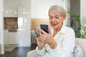 Mature woman with mobile phone on her hands sitting in room and sending messages to her friends and family. Senior woman texting on her mobile phone