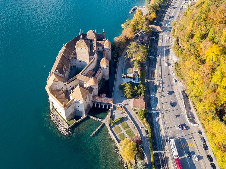 Veytaux, Switzerland - November 01. 2018: Aerial Panoramic View of Chateau de Chillon at Lake Geneva in a golden autumn day, with the Swiss city Montreux at the background