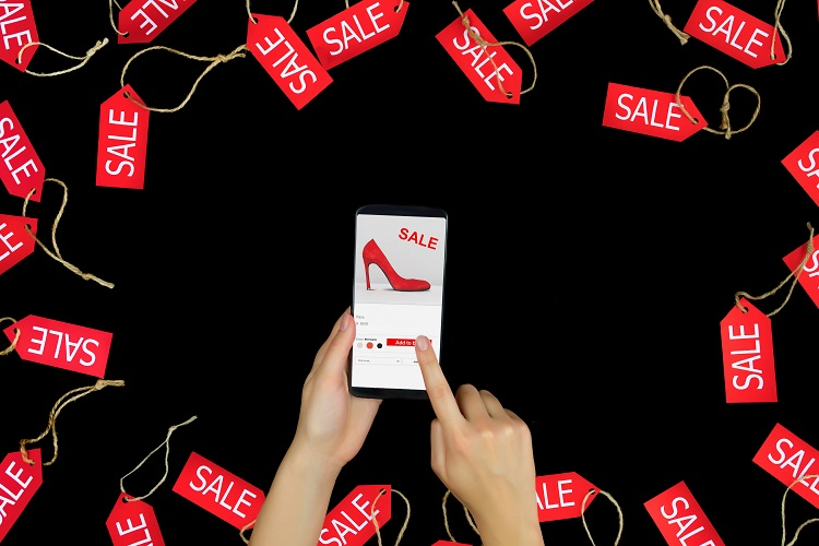 Woman female adult hands with smartphone choosing fashion new red high heels with sale or discount and purchasing buying in internet online shop store in black friday holiday with red sale labels