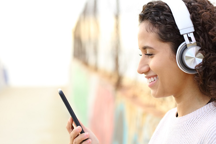 Side view portrait of a happy latina girl listening to music wearing headphones and checking smart phone in the street