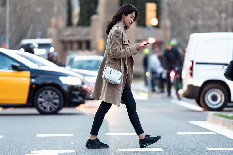 Shot of pretty young woman crossing the street while listen to music with the wireless earphones.